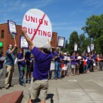 Photo of SEIU member with large sign that says no union busting