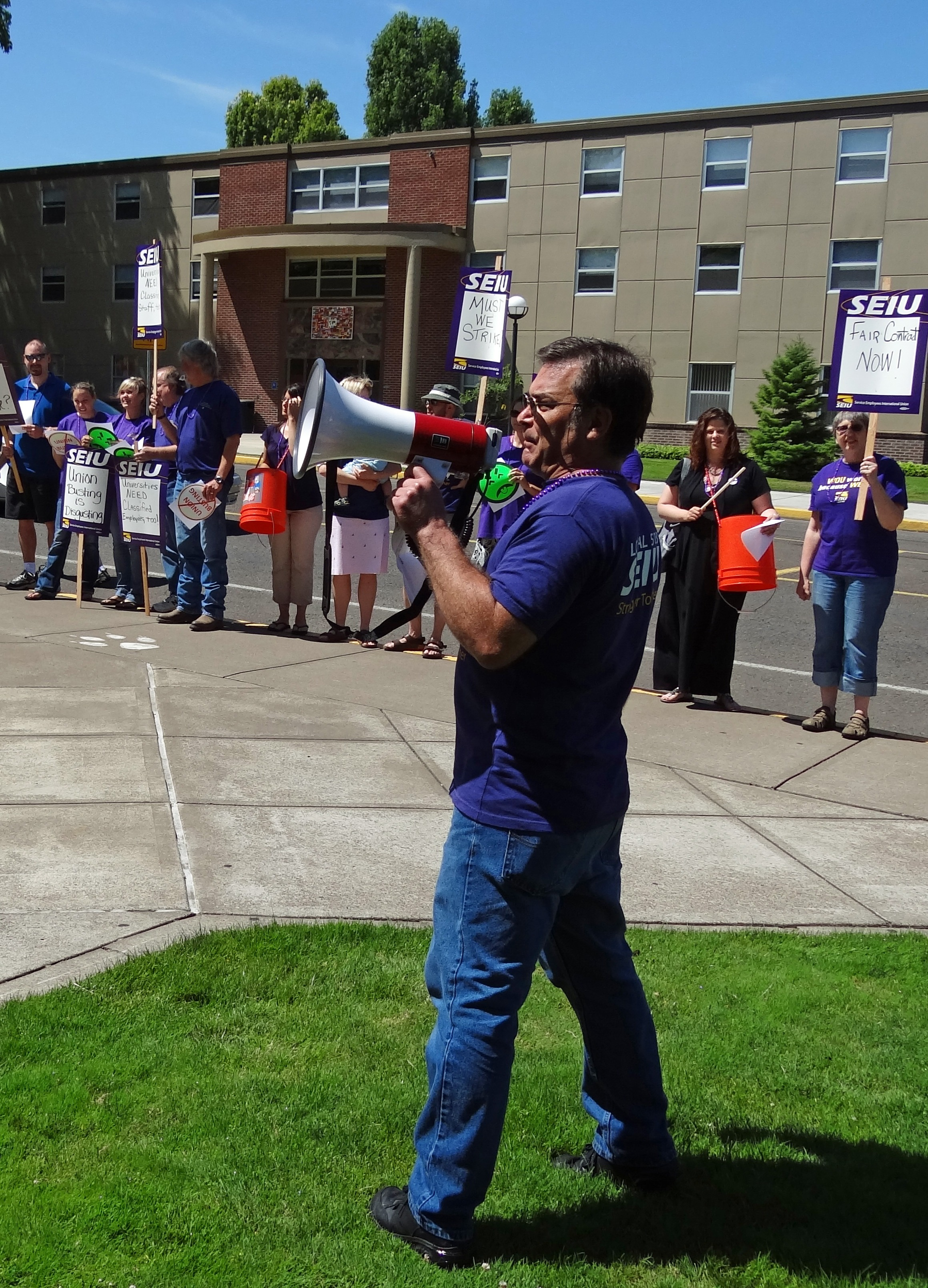 Photo of SEIU member Nat leading chants with megaphone
