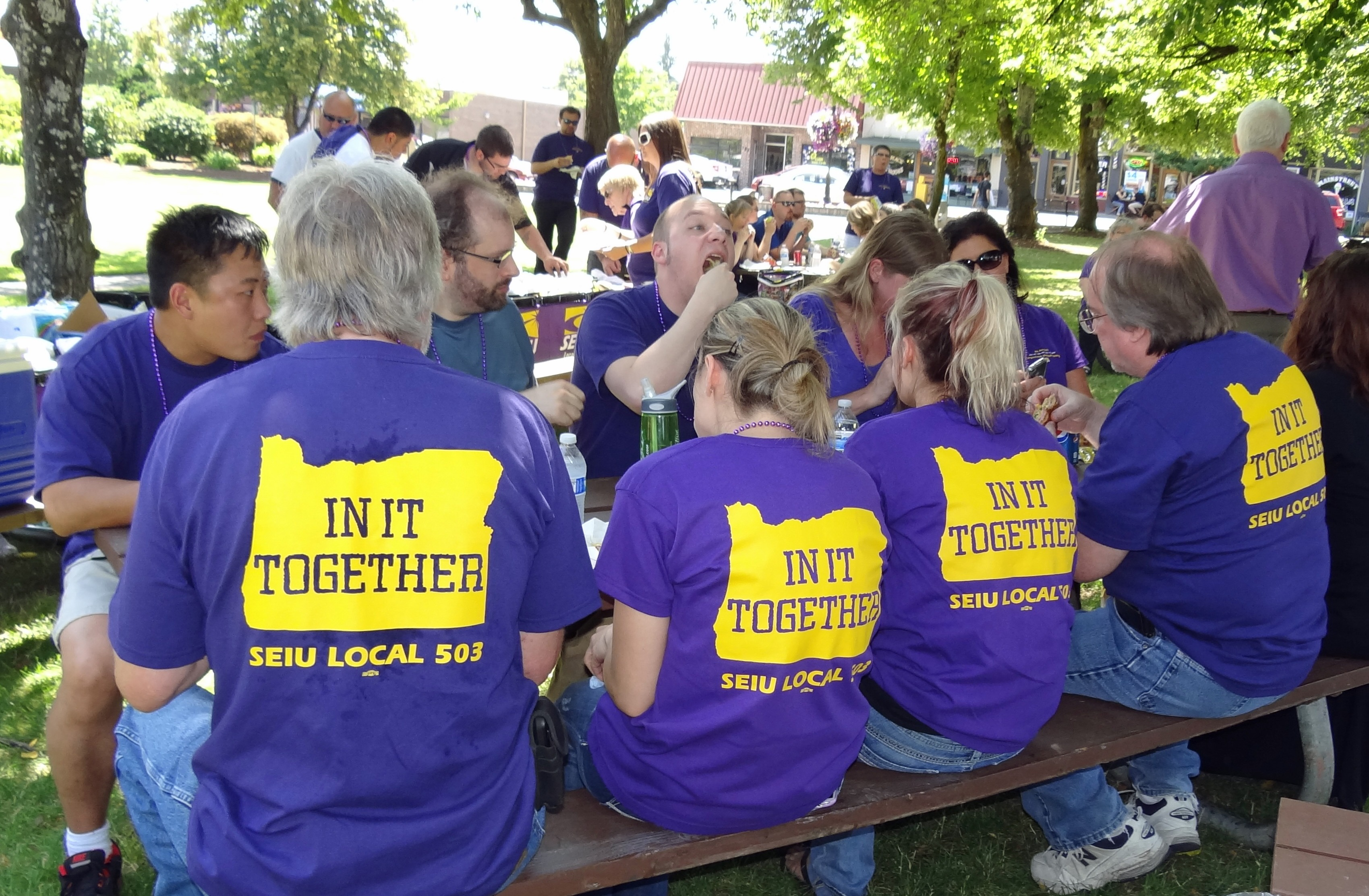 "Photo of 4 SEIU members facing away from camera with ""In It Together"" Oregon logo on their shirts"