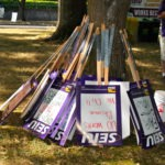 Picture of picketing signs leaned against tree and ready to go