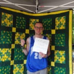 Picture of graduate student with quilt and sign declaring support for SEIU