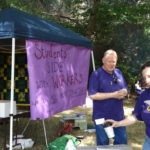 "Picture of a large purple sign, caption: ""Students side with workers, we're all in it together!"""