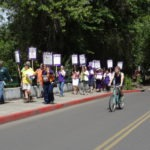 Picture of workers marching on Franklin with picketing signs, drawing the attention of a passing cyclist