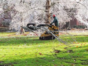 Photographic image depicts a UO grounds crew worker operating a machine to clear campus of debris.