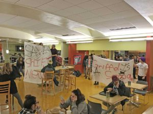 Photographic image depicts people holding signs in protest while occupying a campus dining hall.