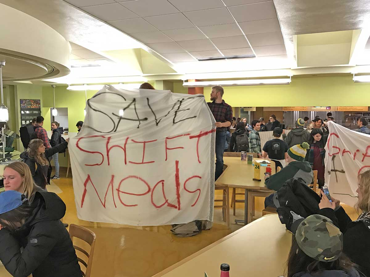 A photographic image depicts people who are students holding signs in protest while occupying a campus dining hall.