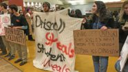 Photographic image depicts people holding signs in protest while occupying a University of Oregon campus dining hall.