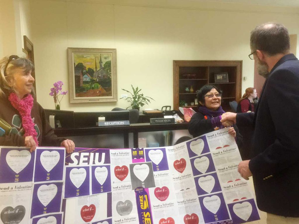 Photographic image depicts three people holding the valentines in the UO president's office.