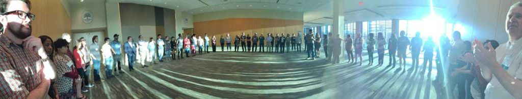 Photographic image is panoramic in format; it depicts people lined up around the edges of a large indoor space in a conference center in Washington, D.C. They participated in the Jobs with Justice Strategy Conference.